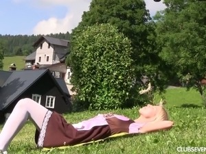 Lovely blonde teen poking tight pussy with sex toy on a lawn outdoor