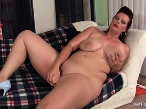 Big breasted plumper drives a long dildo in and out of her tight slit