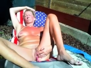 Stacked mature blonde enjoys the sun and plays with her cunt